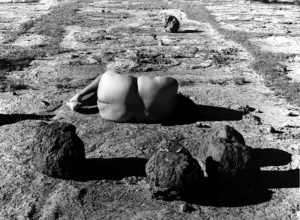 In the center of this black-and-white photograph, a nude woman with medium-dark skin lies on flat and barren land among several large, dark boulders. She is lying on her side with her knees bent toward her chest and her back toward us.