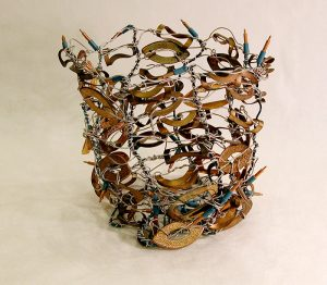 Silver wire and green-string lights are loosely woven into an 8-inch-tall open-weave basket with multiple flat, eye-shaped, copper-colored metal pieces woven into the sides through the wires.