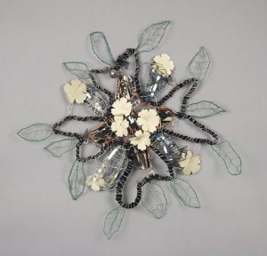 In this wall-mounted sculpture, a cord made of black fabric and tightly wrapped in silver wire is shaped into the outline of a flower with four petals. In the center are four, small, white, flower-shaped objects. Green wire-leaf shapes are attached around the outer edges of the sculpture.