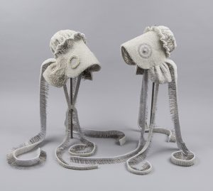 A pair of white bonnets, each with a deep brim, wide ruffle at the neck, and two, long, trailing ribbon ties, are repeatedly pierced-through from the outside with thousands of pearl-headed, metal pins, creating subtle patterns on their exteriors. The inside of the bonnets and ribbon ties reveal the sharp ends of the pins.