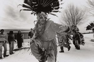 A black-and-white photograph centers on a man wearing a feathered headdress while in mid-action, with his arms raised and knee bent. People, including spectators and other participants of a ceremony, stand behind him on both sides in an outdoor, snowy landscape.