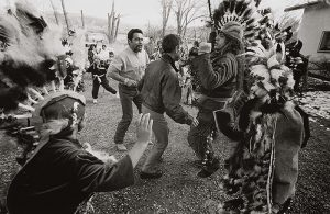 A black-and-white photograph depicts a group of people in an outdoor setting with two men in everyday clothing caught in motion, facing a man who wears a feathered headdress and ceremonial dance clothing and has raised fists. A man in the left foreground also wears a large, feathered headdress and has a raised, open, right hand.