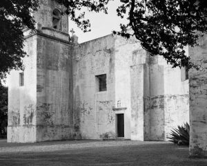A black-and-white photograph of a building made with stone blocks. The roof of the building has a cross, and the walls contain two, square window openings and one arched window opening, through which a hanging bell can be seen. There is a rectangular door to the building on our right and tree branches with leaves cover the left and right, top-quarter of the photograph.