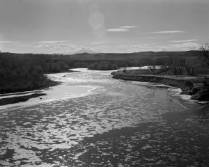 This black-and-white photograph depicts a landscape scene. A river occupies the bottom third of the composition. The sun reflects off the river creating abstract patterns on its surface as it wends its way into the distance. The sky contains small white clouds, and there are hilltops in the background. There are grasses and bushes on both sides of the river and a lens flare appears in the top third of the photograph.