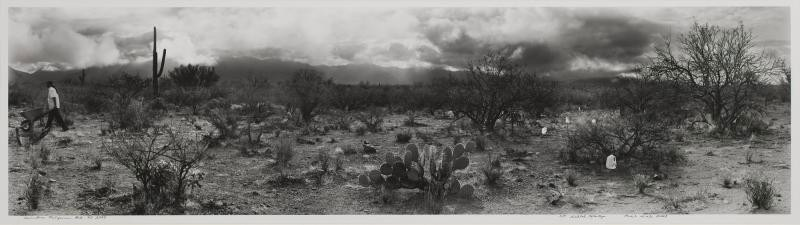 This black-and-white panoramic photograph of a desert scene shows plastic, one-gallon water jugs amidst cacti and other desert plants in the foreground. A man, walking toward our left in the distance, pushes a wheelbarrow.