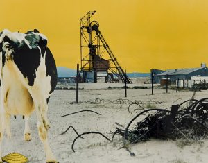 A bright, yellow sky forms the background for this print of a rural scene. A tall, industrial structure, constructed of thin bars, is centered on the horizon. A black-and-white cow stands in the left foreground, with its backend facing us.