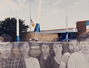 A collaged photograph depicting a one-story, brown building with tall blue-and-white structures resembling rockets in the background and a parking lot in the foreground. Six translucent black-and-white portraits of men and women of varying ethnicities and genders are overlaid across the parking lot.