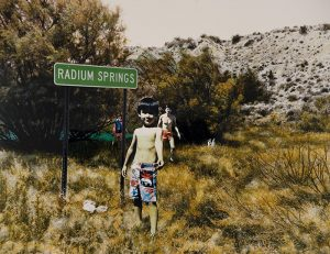 """A collaged photograph depicts a dry desert landscape with tall, sagebrush bushes and a rocky hill. A child with short, black hair, in swim trunks stands next to a green highway sign that reads """"Radium Springs."""" Two people in swimsuits and a small dog stand behind him."""