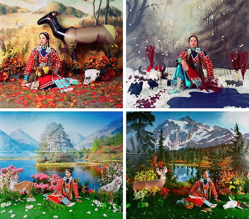 In this series of four photographs, the artist, a Native American woman wearing a red, long-sleeve dress sits on the ground facing us. She is sitting within obviously staged landscapes, surrounded by cardboard cutouts of animals or inflatable animals; fake plants; artificial turf or snow; and a printed, photo backdrop. Each photograph depicts a specific season – spring, summer, fall, or winter. Fall: In this staged fall scene, plastic, orange leaves cover the ground; plastic, orange-and-red flowers surround her; an inflatable deer stands on the right; and a printed backdrop of mountains hangs behind her. Winter: Sitting in styrofoam snow next to a plastic pond, the woman is surrounded by fake, black birds; white, Styrofoam snowballs; an animal skull; and faux, red berries. Behind her is a printed backdrop of trees and plastic snowflakes. Spring: The woman, sitting on artificial, green turf, is flanked by cardboard cutouts of a deer, rabbit, and coyote, and plastic, white flowers are scattered on the ground. Behind her, a printed backdrop depicts a sunny lake with pink, flowering shrubs, and mountains in the distance. Summer: The woman looks slightly toward her left and sits in the center on artificial, green turf in front of a printed backdrop that depicts a sunny mountain scene with a lake. A cardboard cutout of a deer stands to her right, and a plastic skull with horns is laid on the turf near her left. Plastic, yellow-and-orange flowers dot the turf.