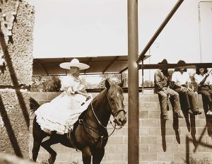 A sepia-toned photograph depicts a woman seated on a dark horse, wearing a long, layered, white dress and a white, wide-brimmed hat. Behind her on her left, three people wearing cowboy hats are seated on a tall brick wall, their faces obscured by a horizontal bar. A vertical bar bisects the photograph between the woman and the people.
