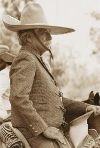 A sepia-toned photograph depicts a portrait of a white-hair mustachioed man, viewed in profile from the waist up, seated in a saddle. The man wears a suit and a tall, wide-brimmed hat that is strapped around his chin. He rests his left hand on the saddle and his right hand on the top of his thigh.