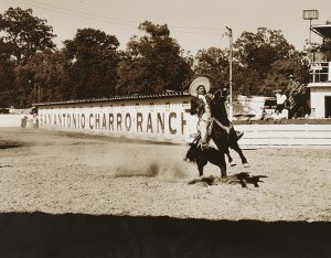 """A sepia-toned photograph of a rodeo arena and a man riding a horse captured in mid-action with its two front legs in the air. The rider wears a black jacket and a wide-brimmed hat. A sign across the corrals behind them reads """"San Antonio Charro Ranch."""""""