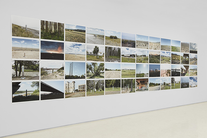 Each of the photographs in this grid of 48 (arranged in 4 rows of 12 photographs each) captures a tall steel obelisk in various settings. Some are urban landscapes with buildings, roads, and underpasses, others show natural landscapes, such as beaches, mountains, forests, and deserts.