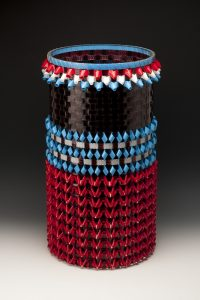 This 2 foot-tall, 14-inch-wide cylindrical basket is made using thin, shiny, strips of brown-black movie film along with folding red, white, and blue lengths of leader film into triangular shapes and weaving all four colors of film together to create patterns of horizontal stripes.