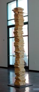 A 10-foot vertical wood beam, carved to look like a column of stacked, folded blankets, sits on a flat, grey metal base. The sculpture is the natural, pale-yellow color of the wood, with carving marks visible on its surface. Rusted metal rods pass through the sculpture horizontally at several points.