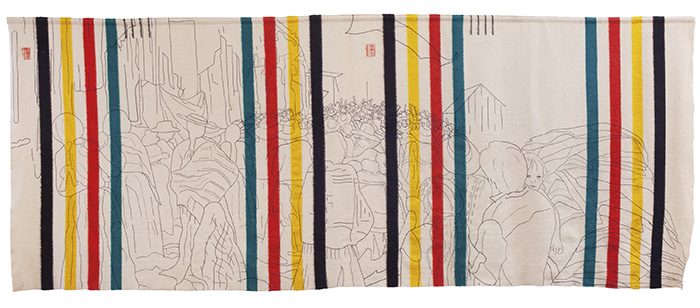 A 15-foot-wide rectangular fabric that has the recognizable sets of Hudson's Bay Blanket stripes (indigo, yellow, red and green) -- one set on each end with two sets equidistant to the center. An outlined scene, stitched in black thread, shows a large group of people, most having their backs to us, except for the face of a child who is a person's arms. People in the distance show raised fists.